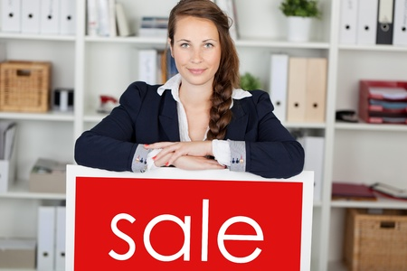 saleslady: Saleslady announcing the start of a seasonal sale standing resting her arms on a large red Sale sign in a shop or office Stock Photo