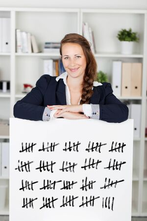 tally: Smiling young business woman with her arms resting on a tally card counting in batches of five struck through with a line Stock Photo