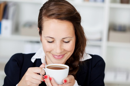 bliss: Beautiful young woman smiling with bliss and anticipation while enjoying a cup of coffee