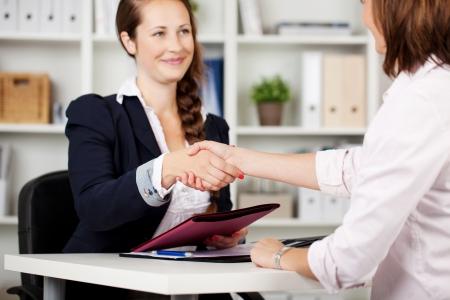 Twee vrouwelijke ondernemers zittend aan een bureau schudden handen op het sluiten van een deal of het bereiken van een akkoord
