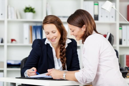 Two attractive female work colleagues having a meeting sitting together at a table in the office discussing a document photo