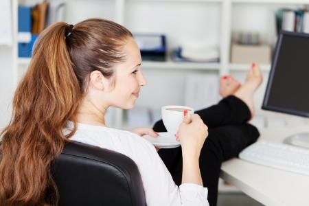 career life: Attractive woman with long brunette hair taking a coffee break in her office with a cup of coffee in her hand and her bare feet up on the counter
