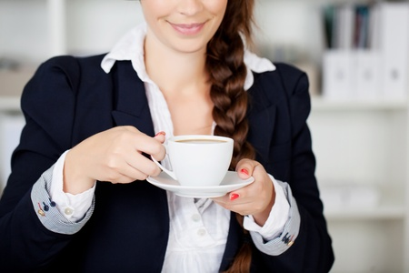 front office: Cropped view portrait off the hands of a stylish businesswoman holding a cup of hot coffee as she stops for a coffee break