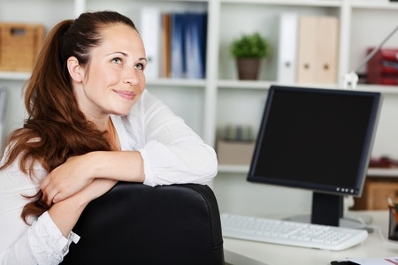 thinks: Smiling woman sitting in front of her desktop while daydreaming