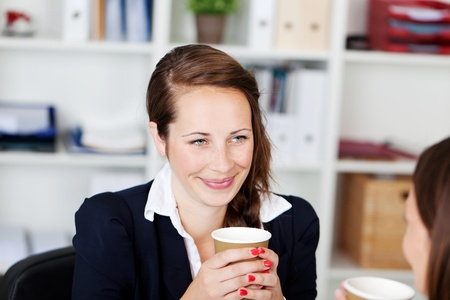 office break: Two businesswomen talking while drinking coffee inside the office