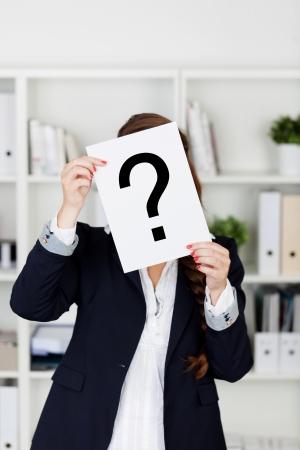 dudas: Empleado de oficina hasta la celebración de un signo de interrogación dibujado en una hoja de papel delante de su cara mientras ella levanta una consulta o indica confusión