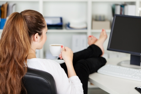 at her desk: Office worker taking a coffee break with her bare feet raised up on the desk and a cup of espresso in her hands, over the shoulder rear view Stock Photo