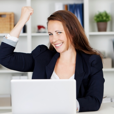 woman sitting with laptop: Image of a happy female executive expressing her joy after achieve her targets.