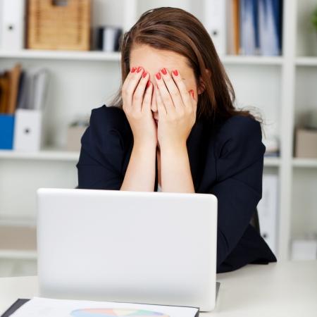 Moe of depressief zakenvrouw zit aan haar bureau achter haar laptop met haar handen voor haar ogen Stockfoto
