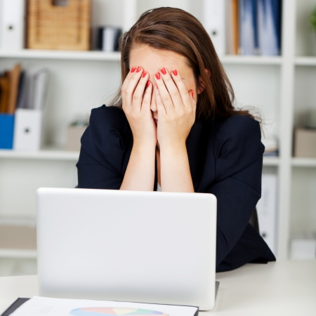 strained: Tired or depressed businesswoman sitting at her desk behind her laptop with her hands covering her eyes