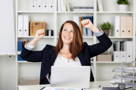 businesswoman: a pretty female expressing herself with her hands in the air after achieving something.