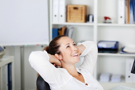 taking a break: a young happy female relaxing on the chair with hands behind her head and a wide smile on her face.
