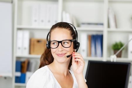眼鏡笑顔のオフィス ワーカーとコール センターまたはクライアント サービス ヘルプ デスクの呼び出しにヘッドセットの応答