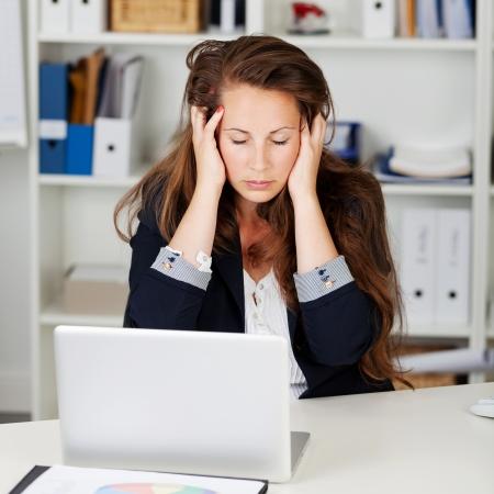 Mujer infeliz que se sienta en su oficina con los ojos cerrados y las manos en la cabeza, ya sea porque está mal o porque está bajo el estrés y la frustración en su trabajo Foto de archivo