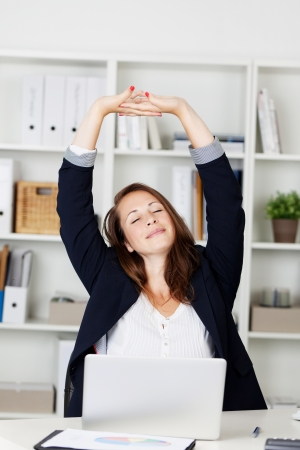 Businesswoman stretching her arms above her head and smiling in pleasure as she sits behind her desk working photo