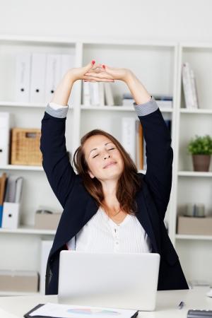 Zakenvrouw stretching haar armen boven haar hoofd en lacht in plezier als ze zit achter haar bureau werkt