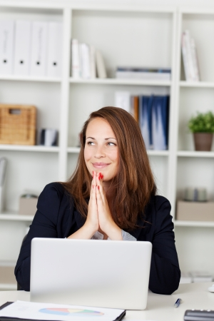 Image of a beautiful young female looking away while working on the laptop and smiling.