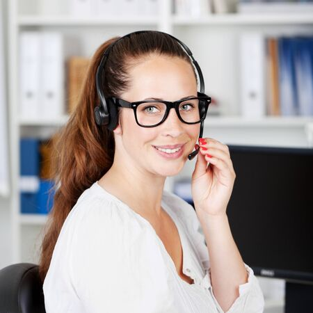 telephonic: Portrait of a charming young female working in a call center or customer care. Stock Photo
