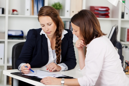 Image of two female co-workers having a discussion on a project. photo