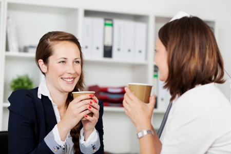 sipping: Image of women executives sipping coffee and having an interesting conversation during a break.