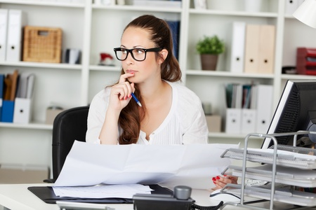 Businesswoman thinking and holding paper works on her table photo
