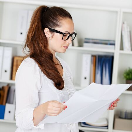seriously: Portrait of businesswoman reading the white paper inside the office