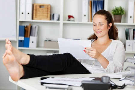 barefoot people: Relaxing woman sitting while reading inside the office Stock Photo