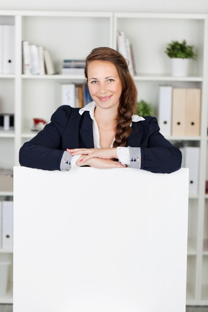 Smiling businesswoman lying her arms on a white board photo