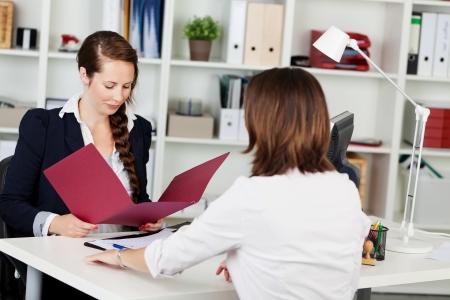 interview job: Atractivo joven ejecutivo empresarial femenino la realizaci�n de una entrevista de trabajo sentado en su escritorio leyendo los candidatos curriculum vitae