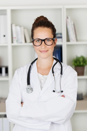 Smiling friendly young female doctor standing in her office at her practice with a stethoscope round her neck and her arms folded photo
