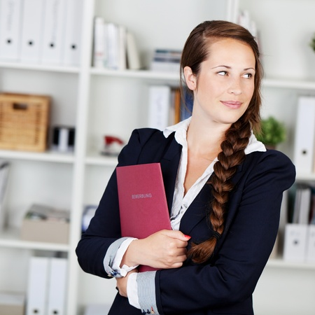 well dressed  holding: Beautiful pensive businesswoman with long plaited brunette jair standing holding a folder and looking back over her shoulder to the right of the screen with a thoughtful expression