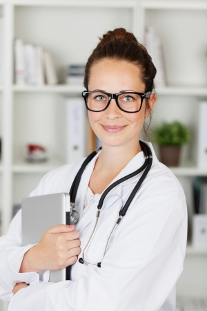 Attractive friendly young female doctor or medical student wearing glasses holding a laptop computer in her arms photo