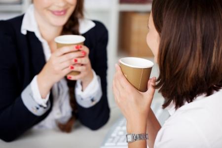 Kantoor koffiepauze met twee vrouwelijke collega's sittng chatten via kopjes koffie