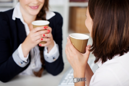Office coffee break with two female colleagues sittng chatting over cups of coffee photo