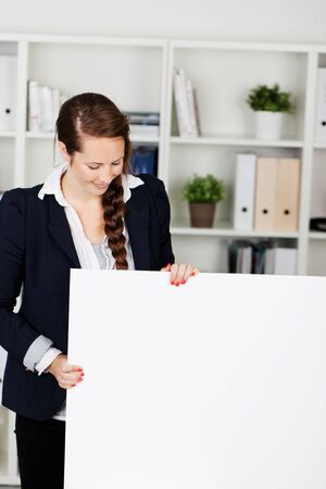 Smart attractive businesswoman standing in her office holding a blank white sign with copyspace for your text photo