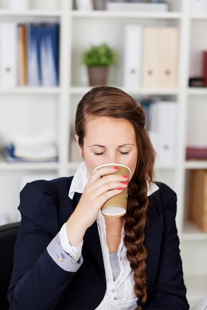 Businesswoman drinking a cup of coffee and sitting in her office photo