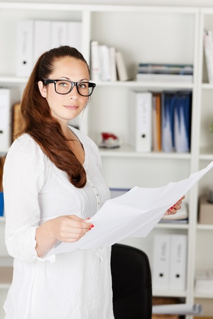 seriously: Image of an attractive businesswoman going through some documents.