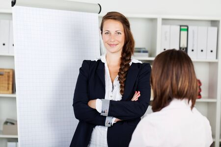 Confident young business woman with a blank white flip chart with copyspace standing smiling at the camera with folded arms photo