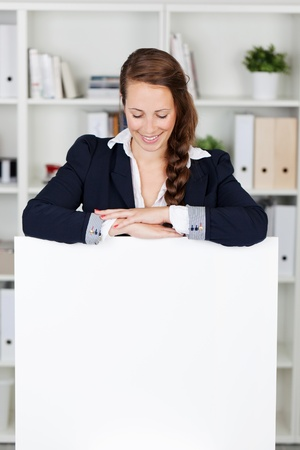 Beautiful smart business woman standing with her arms folded leaning on a blank white sign with copyspace for your text and looking down with a smile photo
