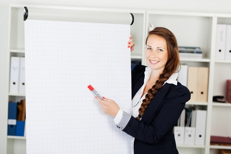 flip chart: Smiling stylish business woman pointing to a blank flip chart with a red marker as she makes a presentation in an office, copyspace for your text or advertisement