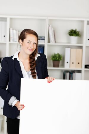 Beautiful young businesswoman with a friendly smile standing in an office holding a blank white placard for your text or advertisement photo