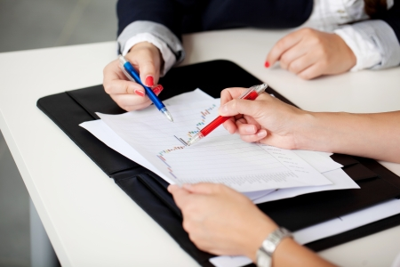 Cropped view of the hands of two women in a business meeting sitting at a table discussing a document and graph while making notes on it with their pens photo