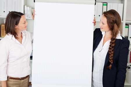 Two attractive confident businesswomen giving a flip chart presentation standing on either side of a large sheet of blank white paper for your text photo