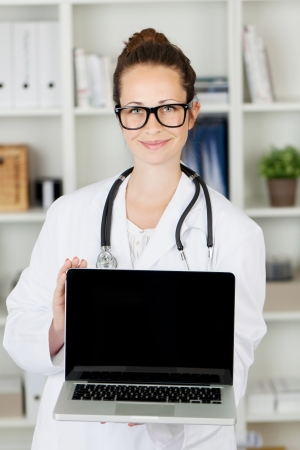Young attractive female doctor holding up a laptop with a blank screen with copyspace for your text in her hands with a friendly smile photo