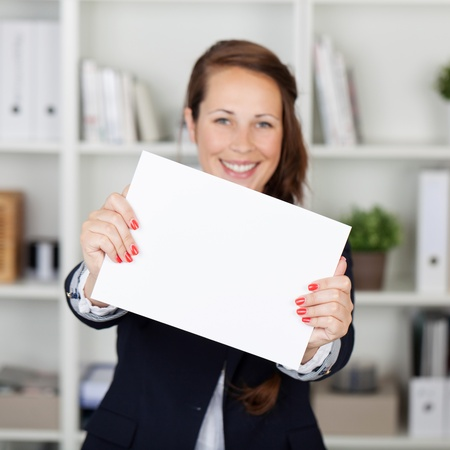 Happy Woman holding a white paper at work photo