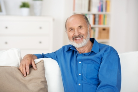 60 years: Smiling friendly senior man relaxing at home sitting on a sofa in his living room looking at the camera