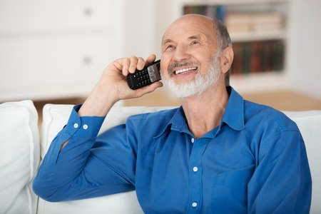 cordless phone: Delighted senior man chatting on a mobile phone while relaxing on a sofa in his living room, natural close up portrait