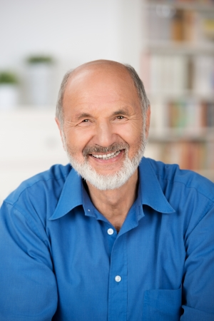 Vertical portrait of a Caucasian cheerful bearded senior man smiling at camera and wearing a blue shirt