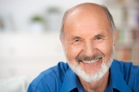 Close up Porträt einer lächelnden attraktiven Senior Mann sucht direkt in die Kamera mit Exemplar