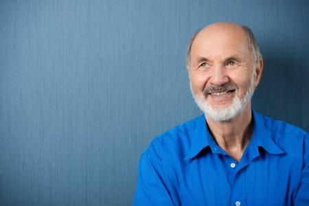 hombres maduros: Hombre reflexivo alto mirando a soñar despierto en el aire con una sonrisa mientras se está en contra de una pizarra verde en blanco con copyspace